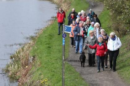 Rebecca Laverty, in the red coat, leads a walk of around 20 pensioners and fellow walkers along the canal path near the Lambhill Stables, Glasgow