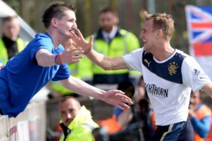 Dean Shiels celebrates with a fan after netting for Rangers