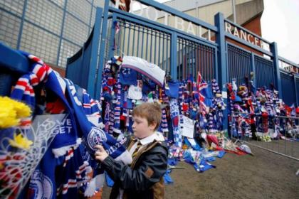 A young fan pays tribute to Rangers legend Sandy Jardine at the Ibrox gates yesterday