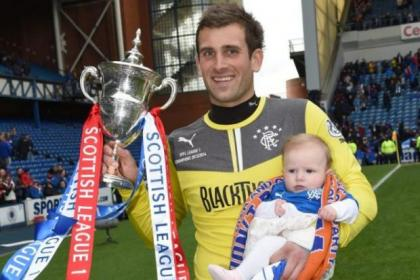 Cammy Bell holding the SPFL League One trophy with his daughter
