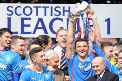 Fraser Aird looks on as Rangers skipper Lee McCulloch holds aloft the SPFL League One trophy