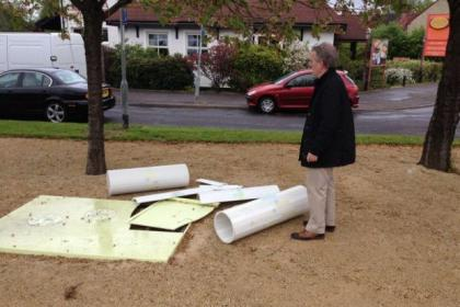 Councillor Bob Burrows inspects the damage to the war memorial.