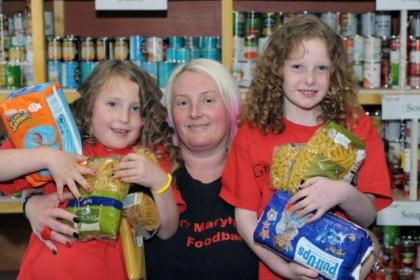 Julie Webster of Maryhill Food Bank is determined not to let people go hungry, and daughter Naomi, 8, and her friend Sophie Kelly, 10, are keen to lend a helping hand                      Picture: Kirsty Anderson