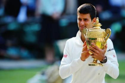 An emotinal Novak Djokovich falls to his knes on the famous Centre Court after his exhausting five-set clash with Roger Federer saw him win through