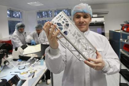Clyde Space Chief Executive Craig Clark shows an engineering model structure of UKube-1