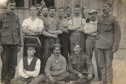 A postcard from Deborah's great-grandfather William, back row, fourth left, in the POW camp and, right, the picture and postcards which were sent to William