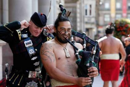 Maori Warrior Te Kooti tries out Piper Hugh McKay's instrument in George Square. Top and right, Singapore's Armed Forces Central Band in action