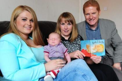 Ashley Burke, with her new 16-day old baby Zander, is been a book 'I Love My Baby' by health visitor Kirsty McLelland and Huw Owen of Unicef