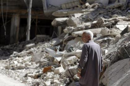 A man walks by damage and debris in Ain Tarma in Syria