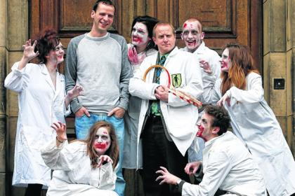 Dr Shaun Killen from the University of Glasgow, second from left, and 'Zombiologist' Ian Alexander, aka Dr Smith (holding tennis racquet/crossbow), with zombies ahead of their show at the Glasgow Science Festival